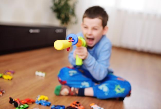 Een klein kind een voorschoolse jongen speelt een schietspel met een speelgoedgeweer op de achtergrond van een lichte speelkamer met speelgoed. een schuimkogel of raket vliegt uit een speelgoedmachinegeweer.