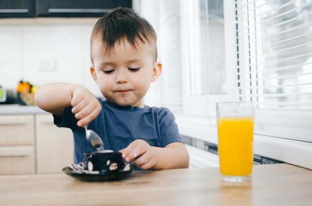 Een klein kind eet een zwarte chocoladetaart, thuis in de keuken
