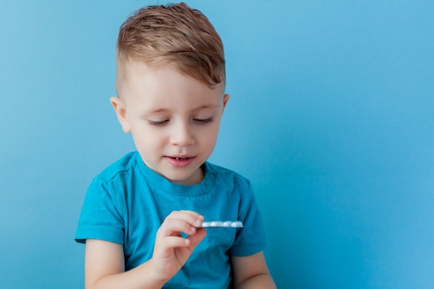 Een klein kind houdt in zijn handpalm een handvol pillen op blauw.