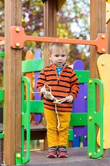 Een klein kind in een gestreepte trui houdt een skelet speelgoed in zijn handen en rijdt van een glijbaan op de speelplaats