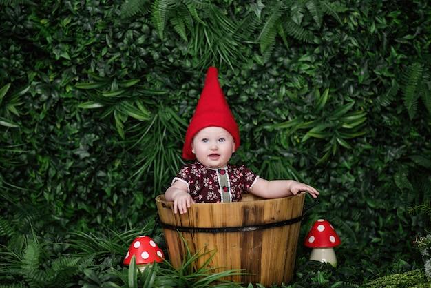 Een klein kind in een kabouterkostuum met een rode pet zit in een houten trog
