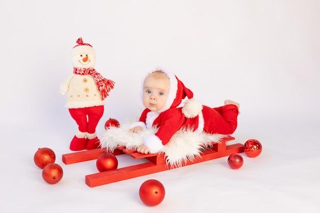Een klein kind in een kerstman kostuum ligt op een geïsoleerde slee