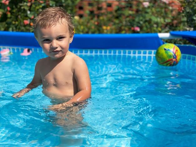 Een klein kind in een opblaasbaar kinderzwembad bij zonnig zomerweer. zomer en vakantie concept.