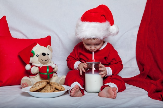 Een klein kind in een rode kerstmuts eet koekjes en melk. kerst portret van een baby in een rode kerstmuts.