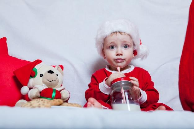 Een klein kind in een rode pet eet koekjes en melk. kerstfotografie van een baby in een rode pet.
