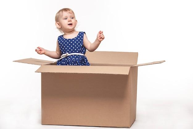 Een klein kind in kartonnen dozen op wit oppervlak