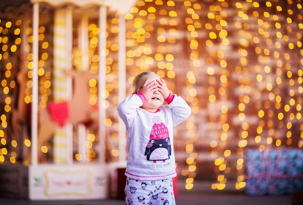 Een klein kind in kerstpyjama staat met zijn ogen dicht met zijn handen. hoge kwaliteit foto