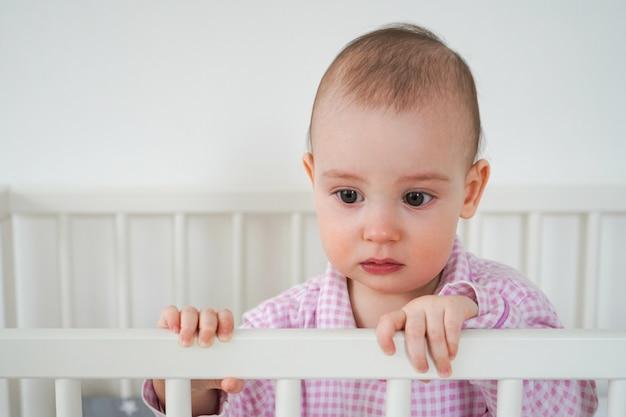 Een klein kind in roze pyjama staat in de wieg. de jongen werd wakker en wacht tot zijn ouders hem uit de wieg trekken. baby begint te huilen
