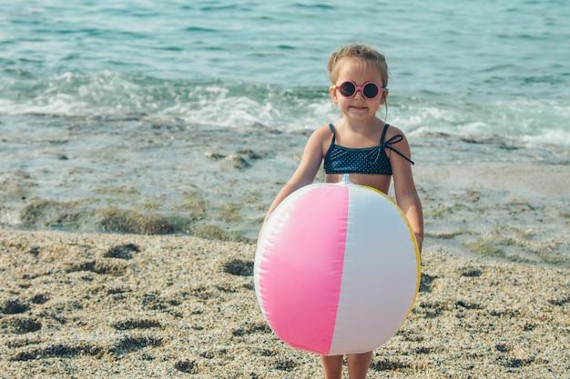 Een klein kind in zonnebril speelt met een opblaasbare bal op het zand. meisje op het strand. zomervakantie aan zee. reis naar warme landen
