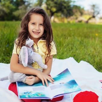 Een klein kind is een boek aan het lezen en glimlachen. plein. het concept
