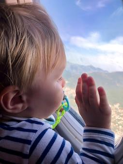 Een klein kind kijkt in het raam van een vliegtuig. toerisme concept.