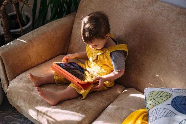 Een klein kind kijkt naar tekenfilms op een tablet terwijl hij alleen thuis op de bank zit.