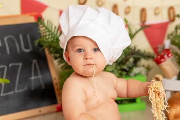 Een klein kind kookt in een hoed in de keuken tussen de producten en eet spaghetti met zijn handen