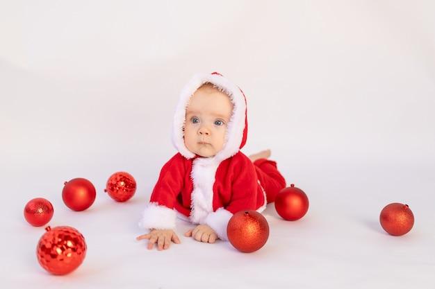Een klein kind ligt in een kerstman kostuum in de studio