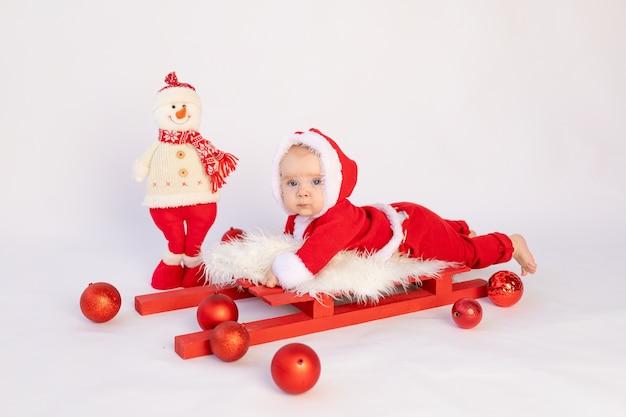 Een klein kind ligt in een kerstman kostuum op een rode slee, kerstconcept