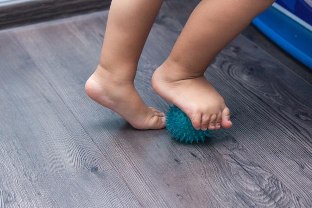 Een klein kind masseert zijn voeten terwijl hij op de masserende bal staat
