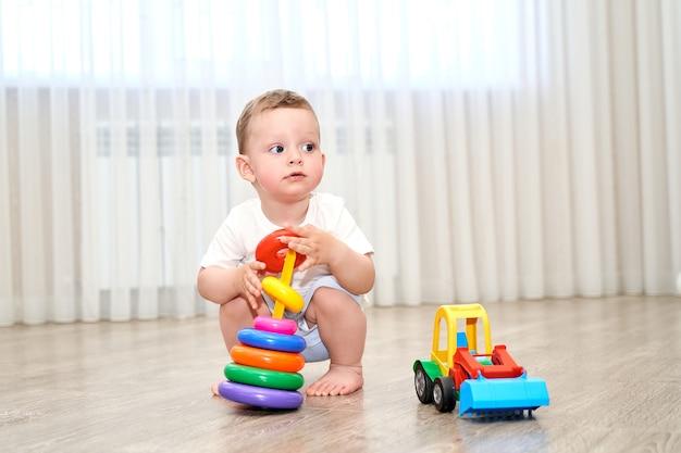 Een klein kind met blauwe ogen speelt in de speelkamer.