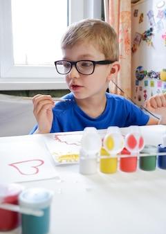 Een klein kind met bril, tekenen met verf. creativiteit van kinderen thuis.