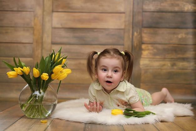 Een klein kind met een boeket gele tulpen. een jongen met een geschenk van bloemen in een vaas. een cadeau voor meisjes op vrouwelijke vakantie met gele tulpen op de vloer.