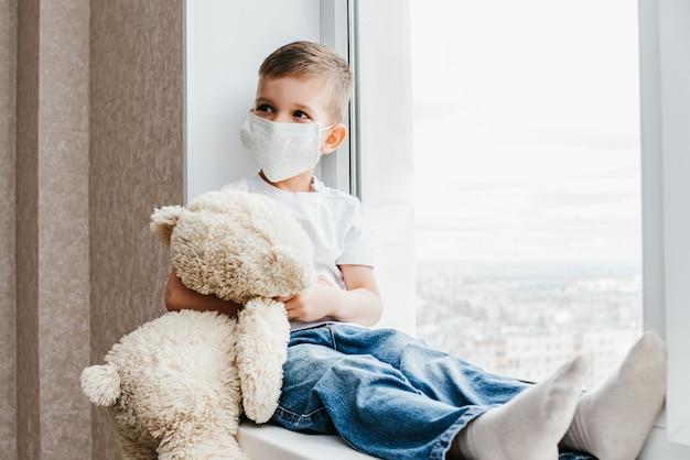 Een klein kind met een masker zit thuis in quarantaine en kijkt uit het raam op een plek met een teddybeer. preventie van coronavirus en covid - 19. concept