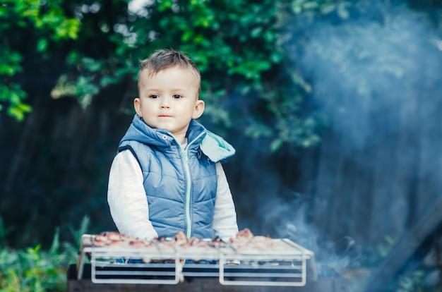 Een klein kind op de eigen barbecue op de grill helpt