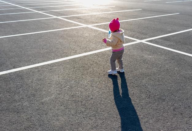 Een klein kind rent op de parkeerplaats tegen de ondergaande zon in