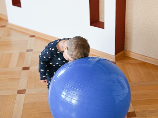 Een klein kind speelt met een bal. baby die zijn hoofd op een bal bonst