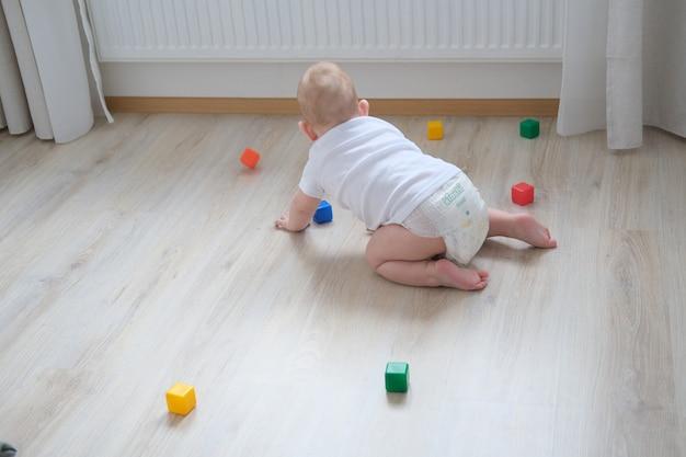 Een klein kind speelt op de grond met gekleurde kubussen en bouwt er een piramide van.