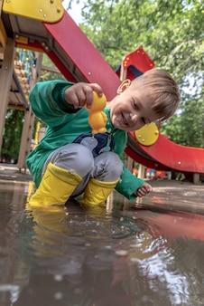 Een klein kind speelt zittend in een plas bij regenachtig weer