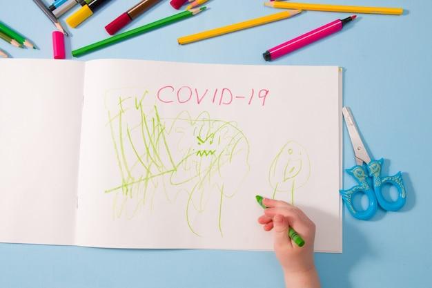 Een klein kind tekent groen waskrijt in een album