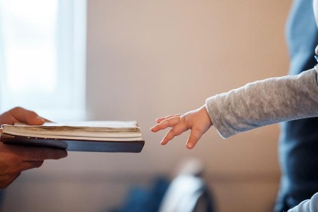 Een klein kind trekt zijn hand naar de bijbel