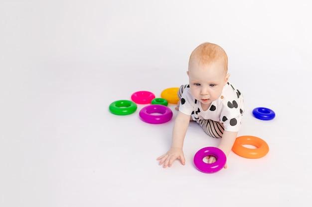 Een klein kind van 8 maanden kruipt op een witte geïsoleerde achtergrond met speelgoed, vroege ontwikkeling van kinderen tot een jaar, een plek voor tekst