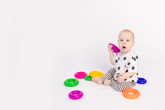 Een klein kind van 8 maanden speelt op een witte geïsoleerde achtergrond, vroege ontwikkeling van kinderen tot een jaar, plaats voor tekst