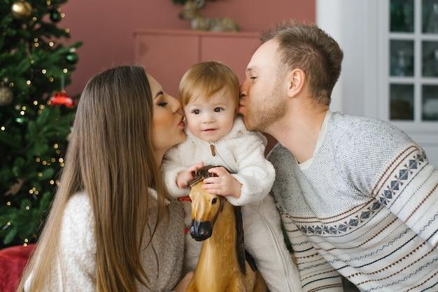Een klein kind van een jaar zit op een houten paard bij de kerstboom. zijn ouders zitten naast hem en kussen hem op de wangen. gelukkig familieportret