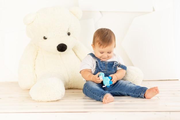 Een klein kind van zes maanden oud in een spijkerbroek speelt thuis bij een grote teddybeer