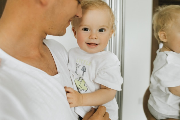 Een klein kind verheugt zich in de handen van zijn vader