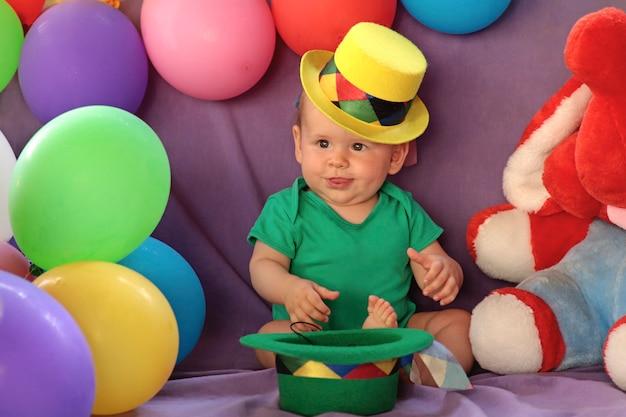 Een klein kind zit in een leuke feestelijke sfeer met ballonnen en gele hoed.