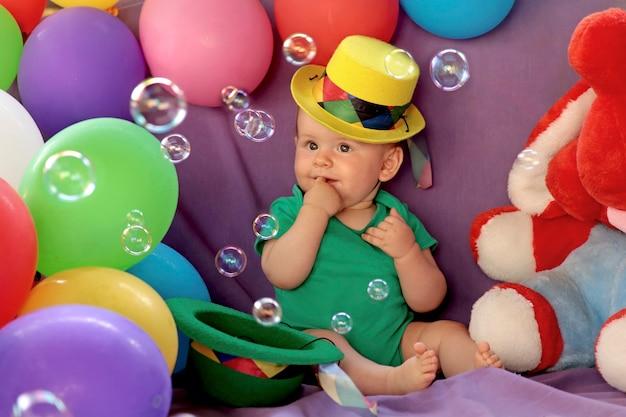 Een klein kind zit in een leuke feestelijke sfeer met ballonnen en kijkt naar zeepbellen.