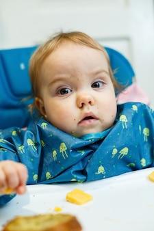 Een klein kind zit in een voedingsstoel en eet voor het eerst brood. gezicht in kruimels