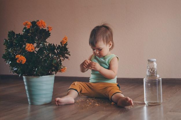 Een klein kind zit op de grond naast een grote bloem in een pot en bloeit met water. meisje scheurt een plant af