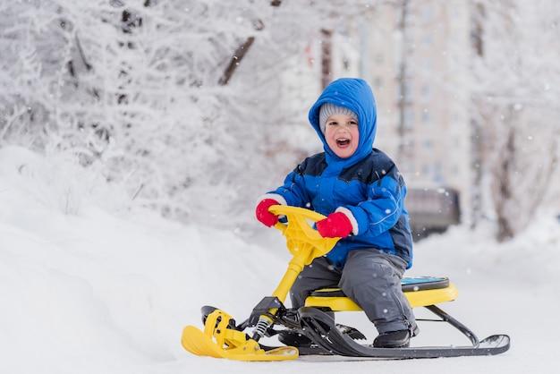 Een klein kind zit op een sneeuwscooter in de winter