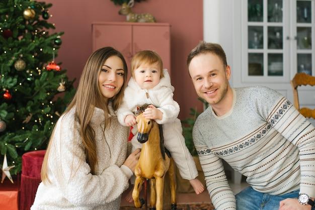 Een klein kind zittend op een houten paard in de buurt van de kerstboom naast haar ouders