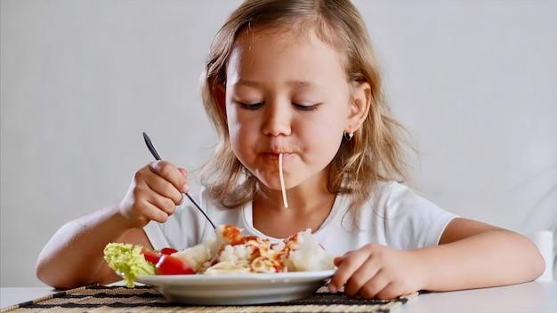 Een klein kindmeisje eet thuis spaghetti