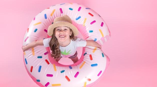 Een klein kindmeisje in vrijetijdskleding die op een opblaasbare cirkel van de doughnut ligt. roze achtergrond. bovenaanzicht. zomer concept.