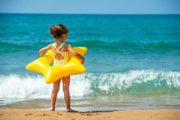 Een klein kindmeisje van 3 jaar staat met een gele zwemring in de vorm van een zeester en kijkt naar de zee. achteraanzicht.