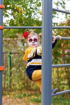 Een klein kleutermeisje met painted face, beklom de zweedse muur in de speeltuin, viert halloween of mexicaanse dag van de doden.