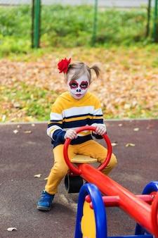 Een klein kleutermeisje met painted face, rijdt op een schommel in de speeltuin, viert halloween of mexicaanse dag van de doden.