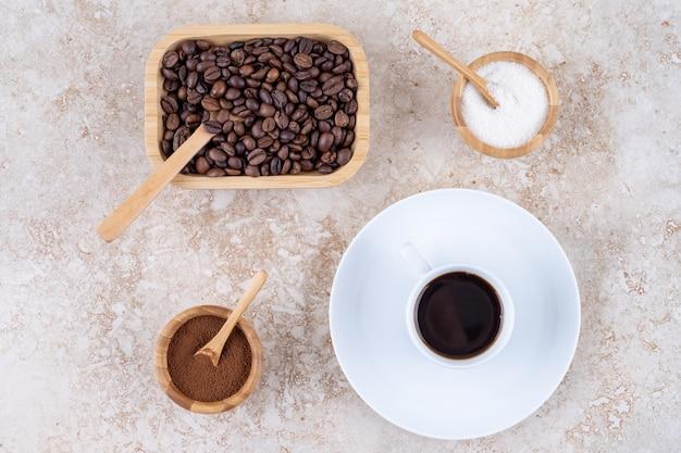 Een klein kommetje suiker naast verschillende soorten koffie