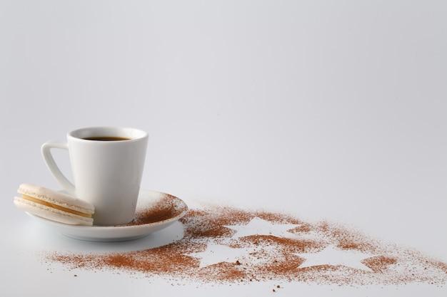 Een klein kopje koffie en cacaopoeder op witte tafel