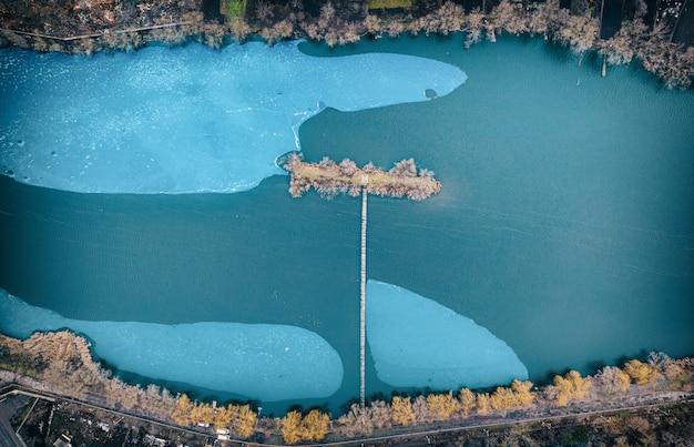 Een klein kunstmatig eiland in het midden van de rivier, met een lange oude houten molen. stukken ijs drijven op het water.